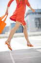 Orange dressed woman with shopping bag - ZEF002124