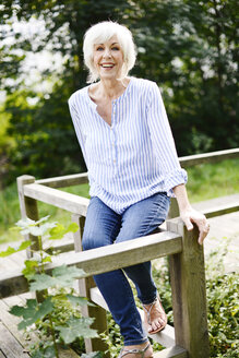 Portrait of smiling white haired senior woman sitting on wooden railing - VRF000130