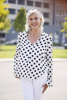 Portrait of smiling senior woman wearing white blouse with black dots - VRF000127
