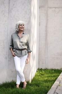 Smiling white haired senior woman leaning against concrete wall - VRF000122