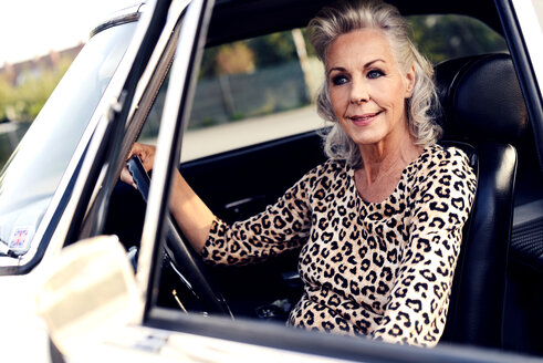 Portrait of smiling white haired senior woman sitting in her vintage car - VR000119