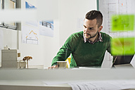 Young man at desk looking at architectural model - UUF002786