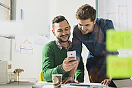 Two smiling young men in office looking at cell phone - UUF002788