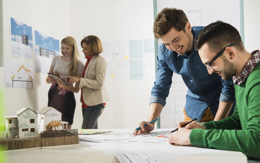 Young architects in office looking at construction plan - UUF002814