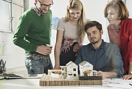 Group of architects in office with architectural model - UUF002816