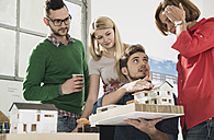 Group of architects in office with architectural model - UUF002817