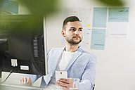 Young businessman in office with computer and cell phone - UUF002827