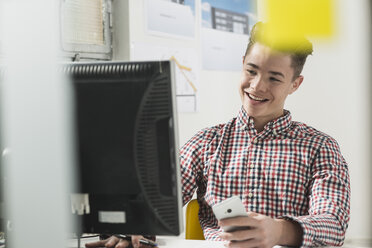 Smiling young man at desk with computer and cell phone - UUF002855