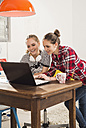 Two female friends using laptop at home - UUF002739