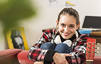 Portrait of smiling young woman with headphones at home - UUF002771