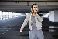 Man wearing hooded jacket training with kettlebell - MAD000110