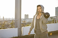 Man wearing hooded jacket training with kettlebell - MAD000116