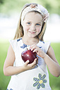 Portrait of smiling little girl with hair-band holding red apple - ZEF002784