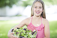 Portrait of a smiling girl holding a bowl of salad - ZEF002754