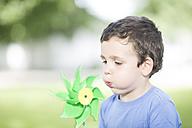 Portrait of little boy blowing paper windmill - ZEF002756