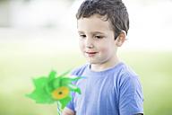 Portrait of little boy looking at paper windmill - ZEF002757