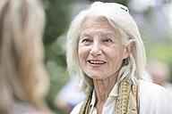 Smiling senior woman in a conversation outdoors - ZEF003456