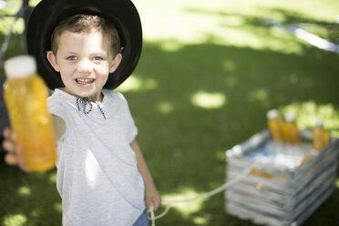 Boy in garden offering a cool drink - ZEF003225