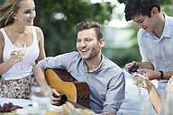 Happy friends with wine and guitar outdoors - ZEF003507