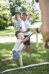 Kids and young man competing in tug of war - ZEF002821
