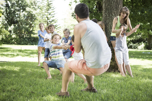 Kids and young man competing in tug of war - ZEF002822