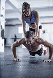Man doing push-ups with woman kneeling on his back - ZEF002623