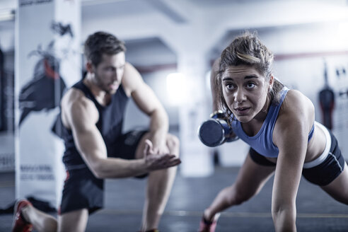 Fitness trainer watching woman doing dumbell push-ups - ZEF002625