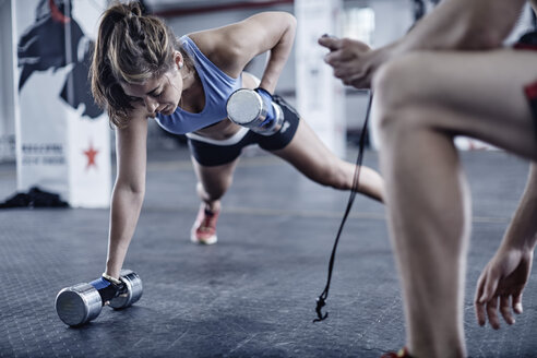 Fitness trainer keeping time with woman doing dumbell push-ups - ZEF002513