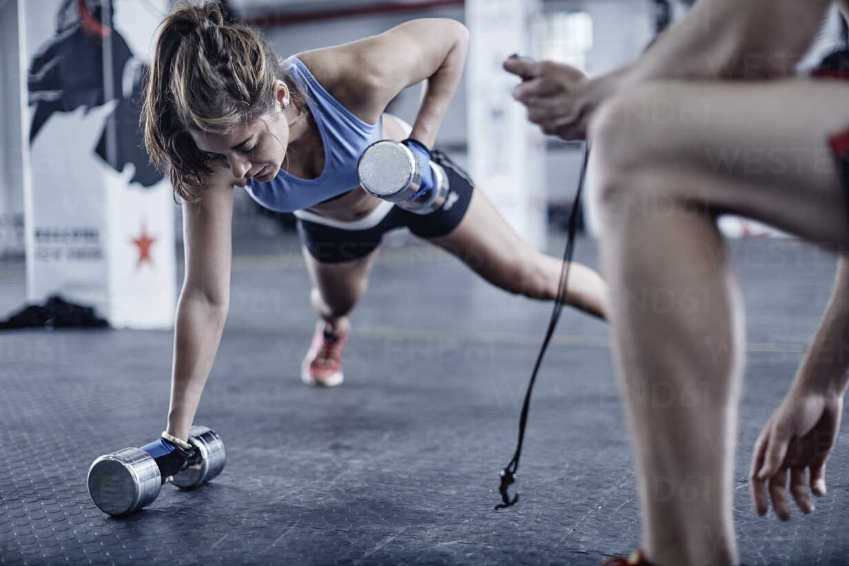 Fitness trainer keeping time with woman doing dumbell push-ups - ZEF002513 - zerocreatives/Westend61