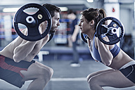 Man and woman doing fitness training with weights - ZEF002629