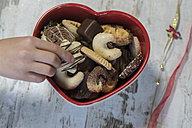 Children's hand taking Christmas cookie from a heart-shaped bowl - SARF001146
