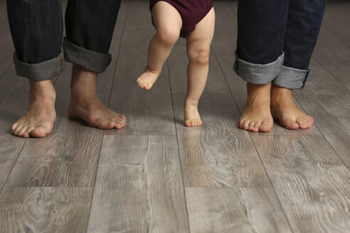 Father, mother and baby girl standing barefoot on floor - SHKF000170