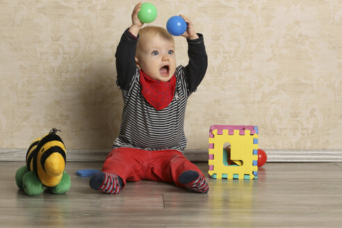 Baby girl with motor skill toy on floor - SHKF000049