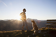 Austria, Tyrol, Unterberghorn, hiker with dog at sunrise - RBF002099