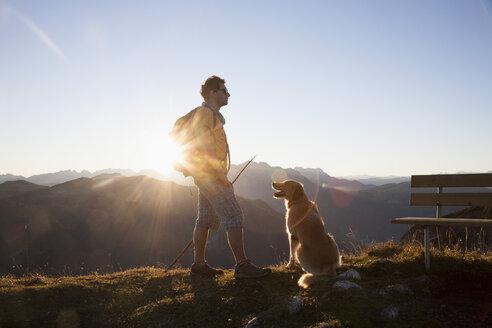 Austria, Tyrol, Unterberghorn, hiker with dog at sunrise - RBF002099