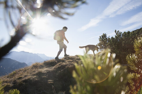 Austria, Tyrol, Unterberghorn, hiker with dog at sunrise - RBF002097