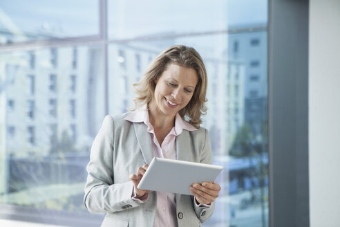 Smiling businesswoman using digital tablet in office - RBF002116