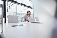 Businesswoman using laptop in conference room - RBF002111