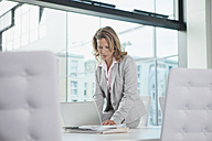Businesswoman using laptop in conference room - RBF002117