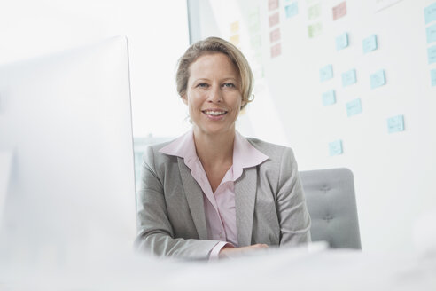 Smiling businesswoman in office - RBF002120