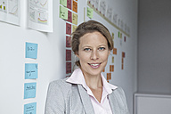 Portrait of businesswoman in office at wall with adhesive notes - RBF002138