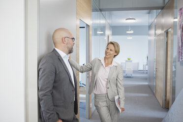 Two colleagues talking on office floor - RBF002144