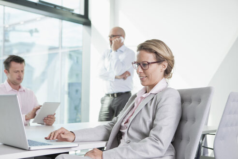 Three businesspeople with laptop, digital tablet and cell phone in conference room - RBF002156