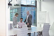 Three businesspeople with laptop in conference room - RBF002163