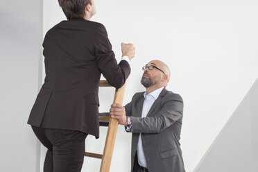 Businessman holding career ladder for colleague - RBF002157