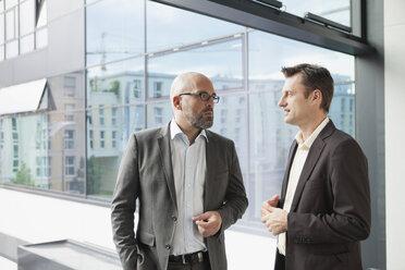 Two businessmen talking in office - RBF002162