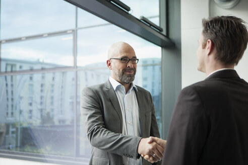 Two businessmen shaking hands in office - RBF002168