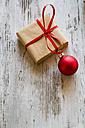 Christmas present with red Christmas bauble on wood - SARF001147