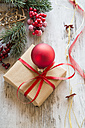 Wrapped Christmas present with red Christmas bauble on wood - SARF001149