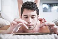 Man lying in bed using digital tablet - ZEF002923